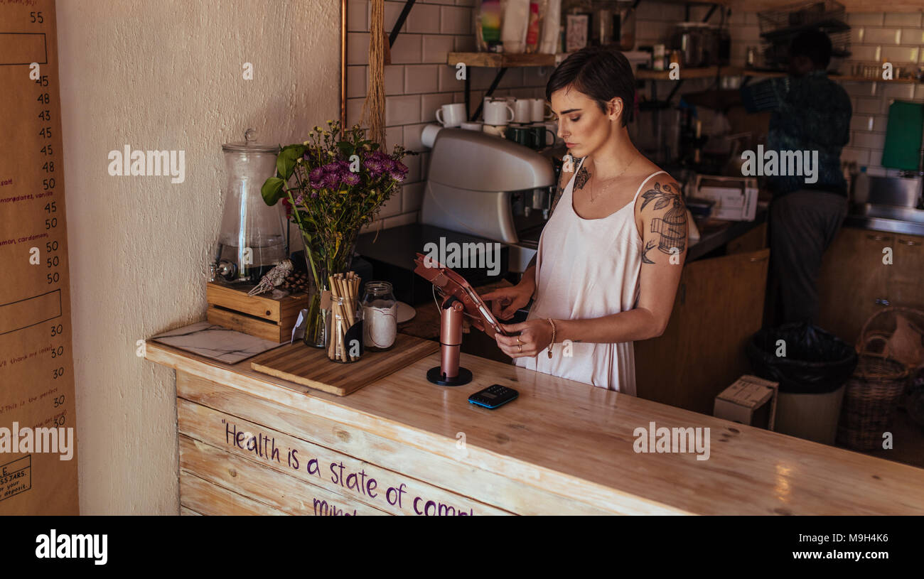 Woman standing at the billing counter of her coffee shop. Coffee shop owner operating the billing machine while a worker prepares coffee in the backgr - Stock Image