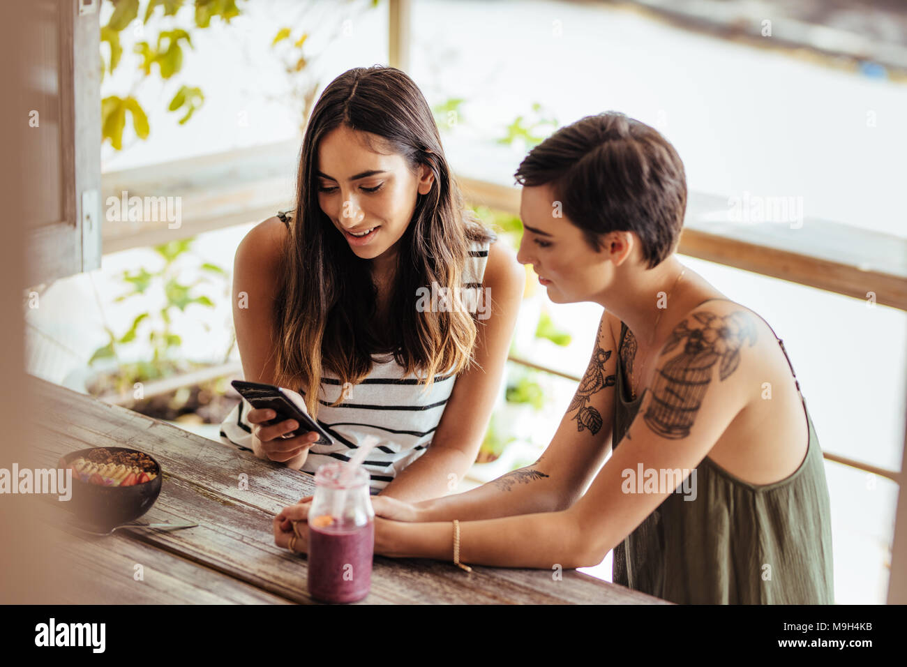 Two women sitting at a restaurant looking at a mobile phone. Women sitting at a restaurant with a smoothie and a dessert bowl on the table. - Stock Image
