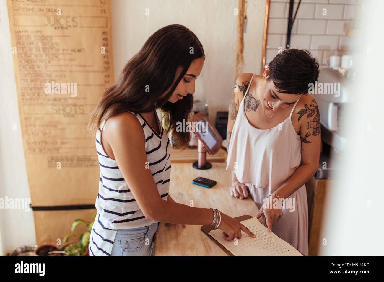 Restaurant owner helping a customer with the menu. Customer ordering food looking at the menu at the billing counter. - Stock Image