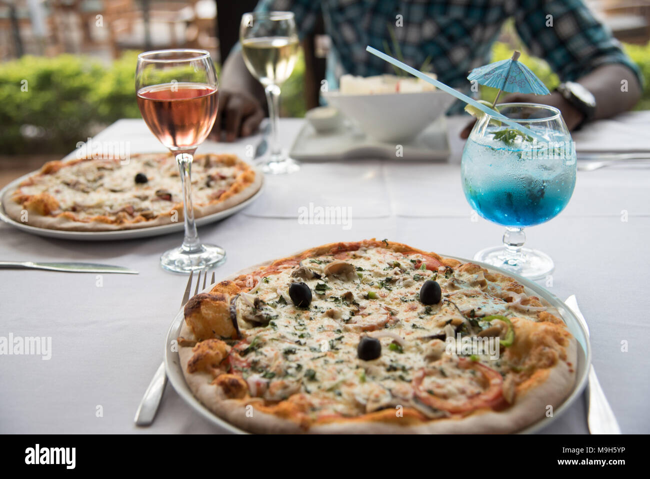 Photo Of Restaurant Table With Two Pizzas And A Salad Also Has Bright Blue Cocktail And Glass Of Pink Wine A Dark Skinned Man Sits In The Background Stock Photo Alamy