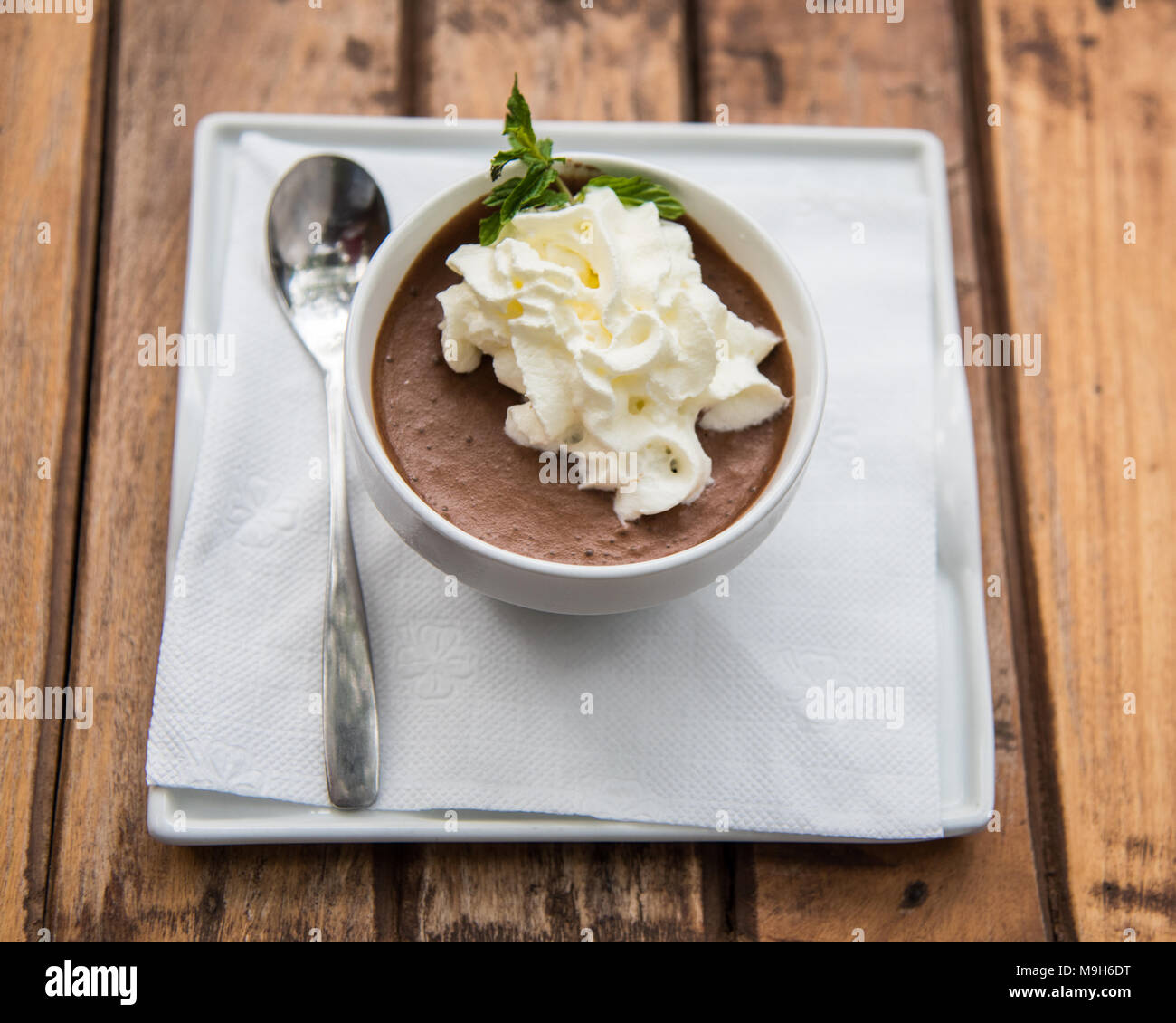 A bowl of brown chocolate mousse, topped with whipped cream sit on brown wood table. - Stock Image
