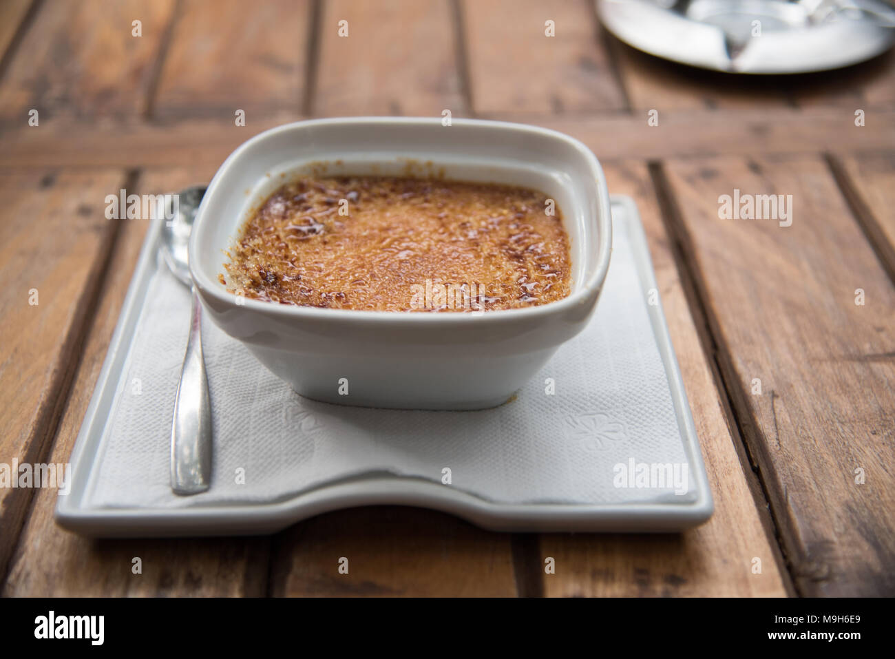 A white bowl holding brown baked flan dessert sits upon a brown wooden picnic table. - Stock Image