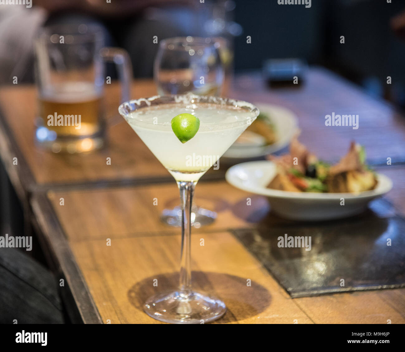 A margarita drink sits on a table in focus. In the background are a variety of alcoholic drinks including beer and wine. - Stock Image