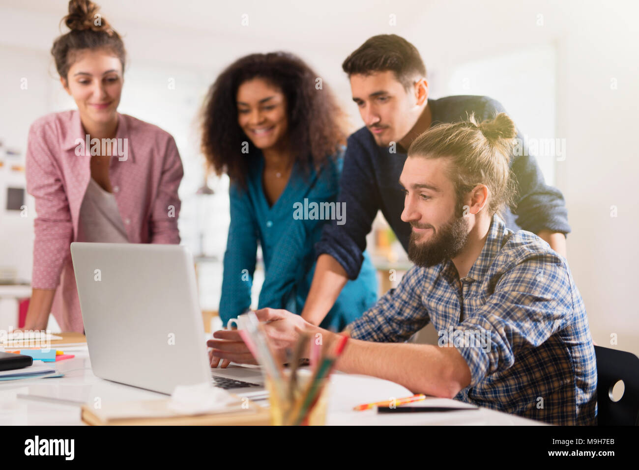 Young multiethnic creative team sharing ideas on a project  Stock Photo