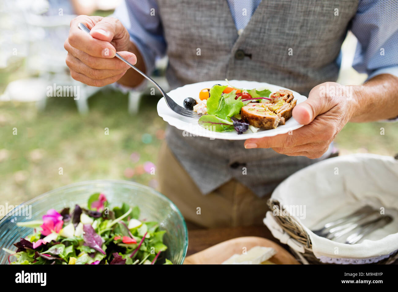Unrecognizable man with a plate with food. Family celebration outside in the backyard. Big garden party. - Stock Image