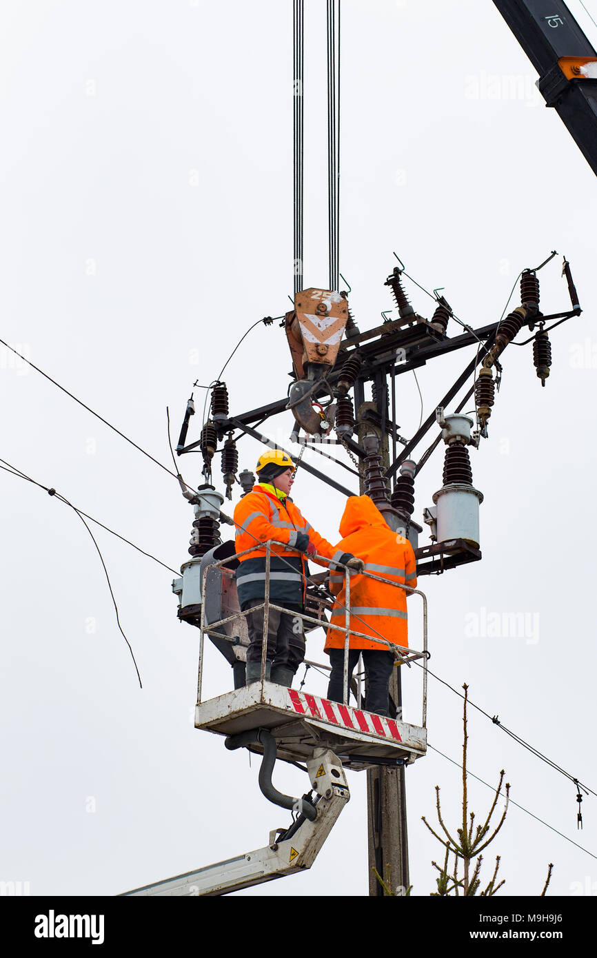 Electricians on a forklift, connecting cables, laying power line ...