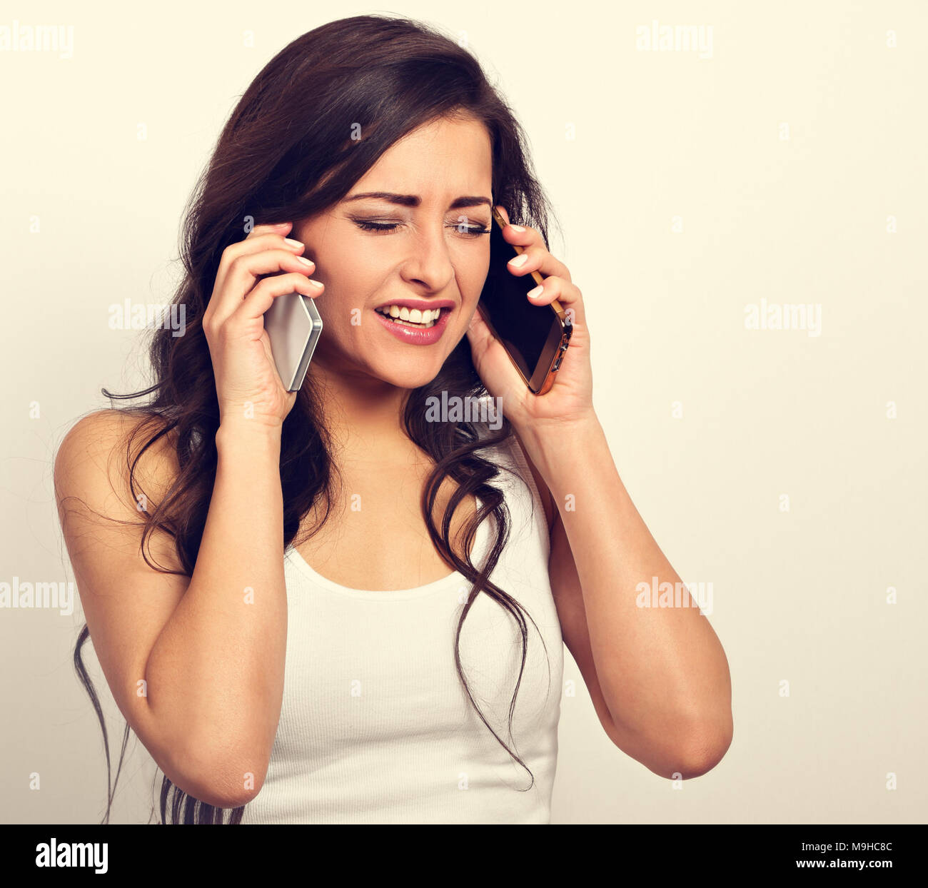 Unhappy angry stressed woman holding two mobile phones near