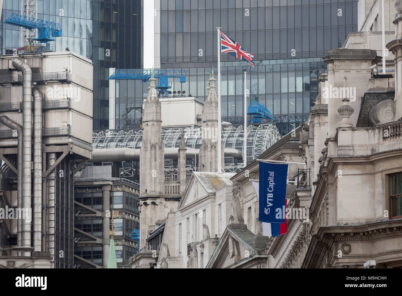 The flags of the Russian Federation and Russian investment Bank VTB Capital hang over banks and other financial institutions in the City of London, the capital's financial district (aka The Square Mile), on 26th March, 2018, in London, England.  VTB Capital operates in London, Singapore, Hong Kong, Sofia, New York, Zug and Frankfurt, with headquarters in Moscow, VTB Group's Corporate Investment Business is a leader in the international investment banking sector in Russia. - Stock Image