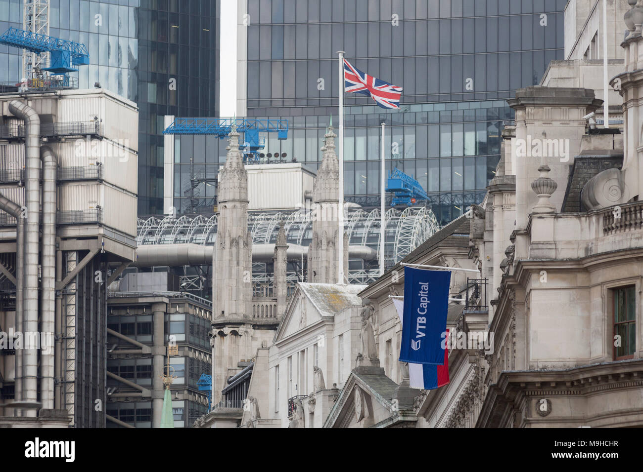 The flags of the Russian Federation and Russian investment Bank VTB Capital hang over banks and other financial institutions in the City of London, the capital's financial district (aka The Square Mile), on 26th March, 2018, in London, England. VTB Capital operates in London, Singapore, Hong Kong, Sofia, New York, Zug and Frankfurt, with headquarters in Moscow. - Stock Image