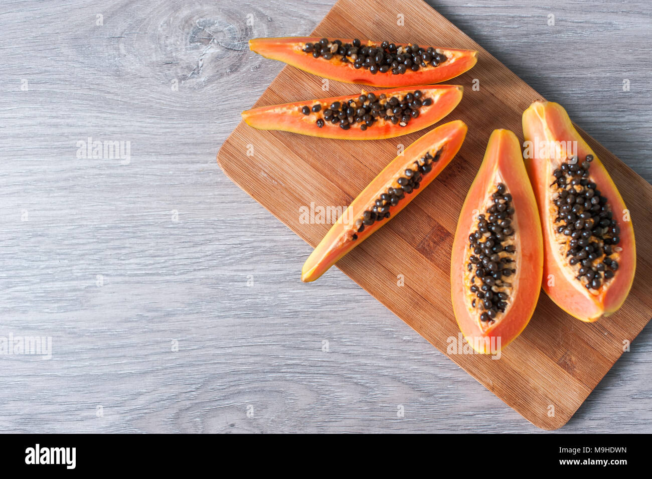 Papaya on wooden background. Healthy food, ripe exotic fruits. The concept of vegetarianism - Stock Image