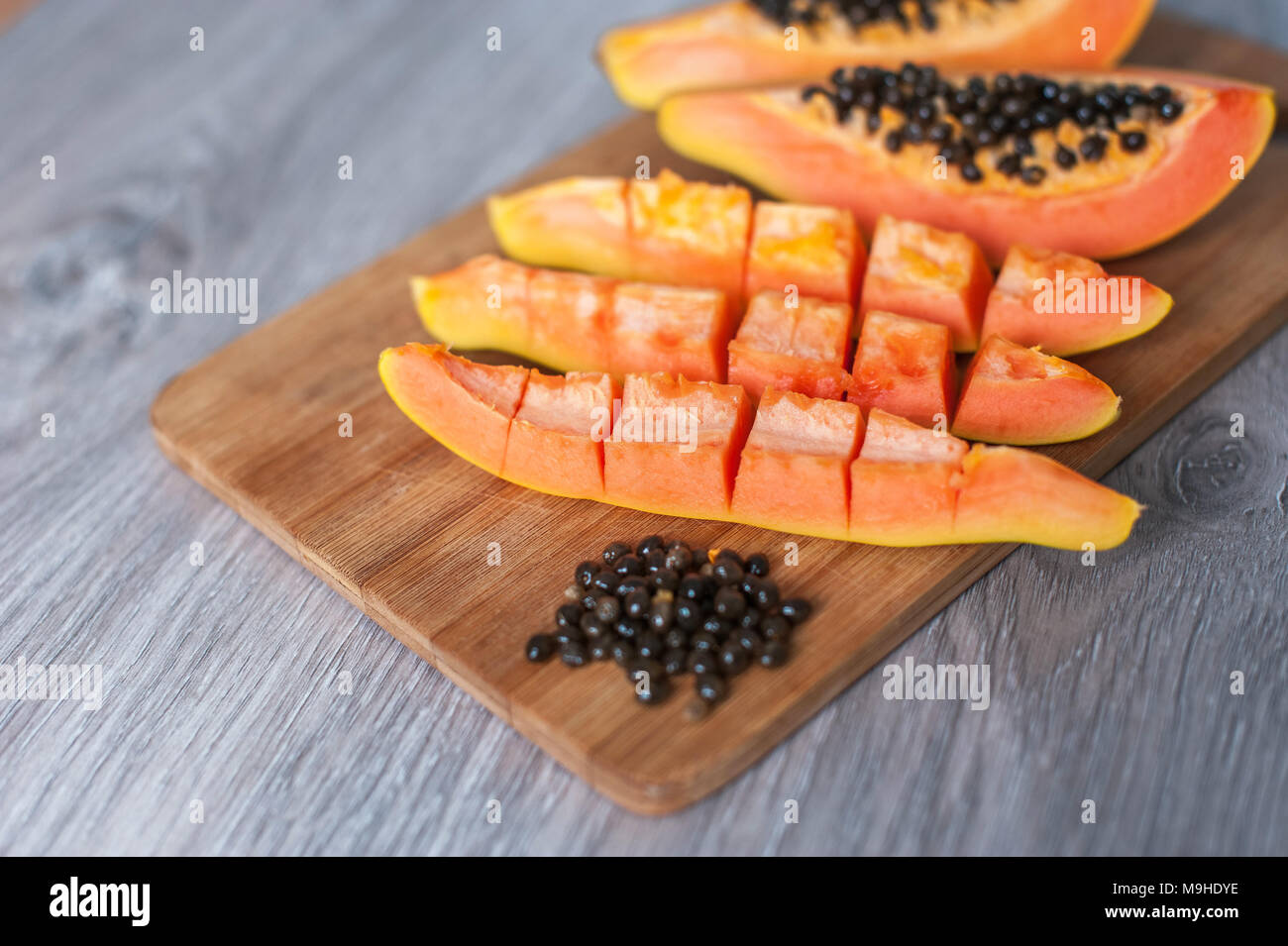 Papaya fruit cut in slices on wooden background - Stock Image
