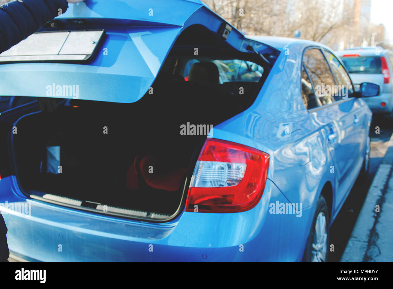 open trunk of the blue car in which the spare child seat is stored - Stock Image