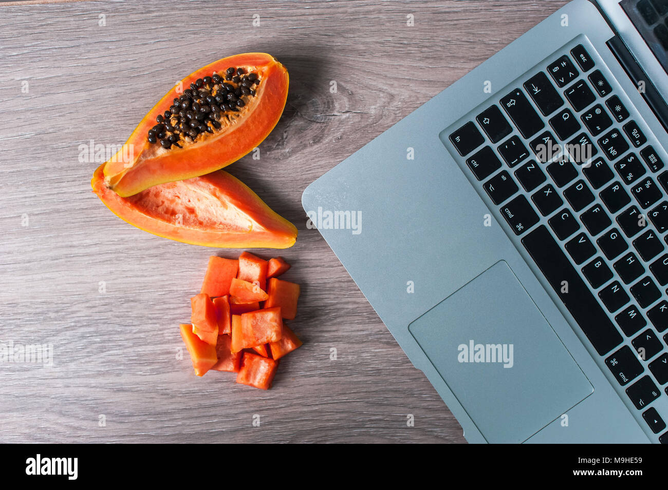 Papaya fruit cut in slices on wooden background and notebook. The concept of remote work. Freelance in exotic countries - Stock Image