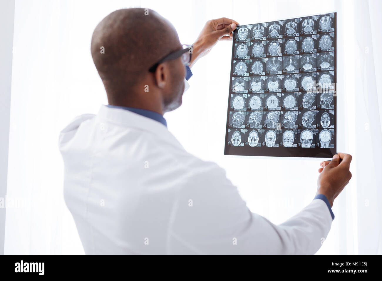 Appealing male doctor evaluating brain imaging - Stock Image
