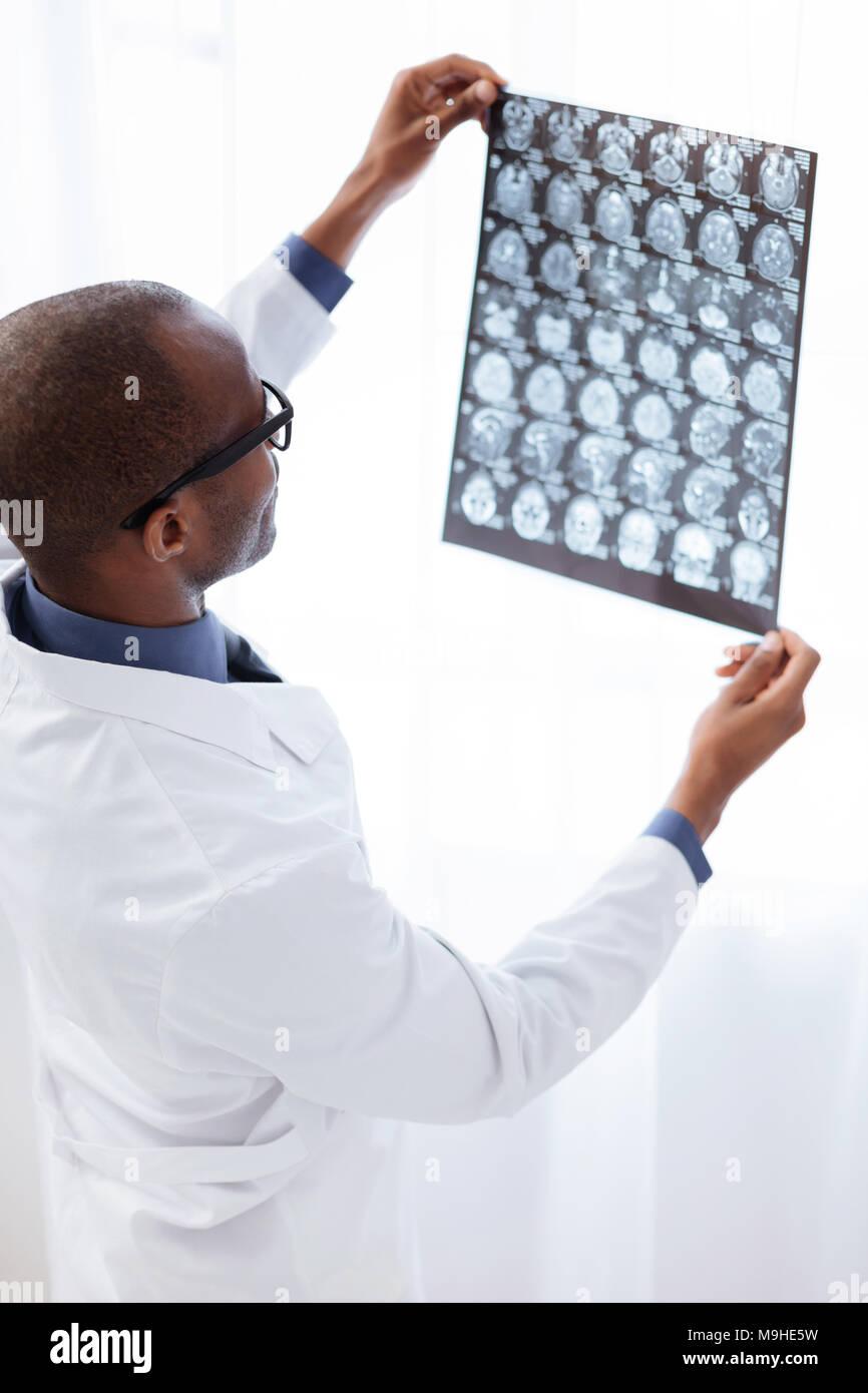 Skillful male doctor examining brain imaging - Stock Image