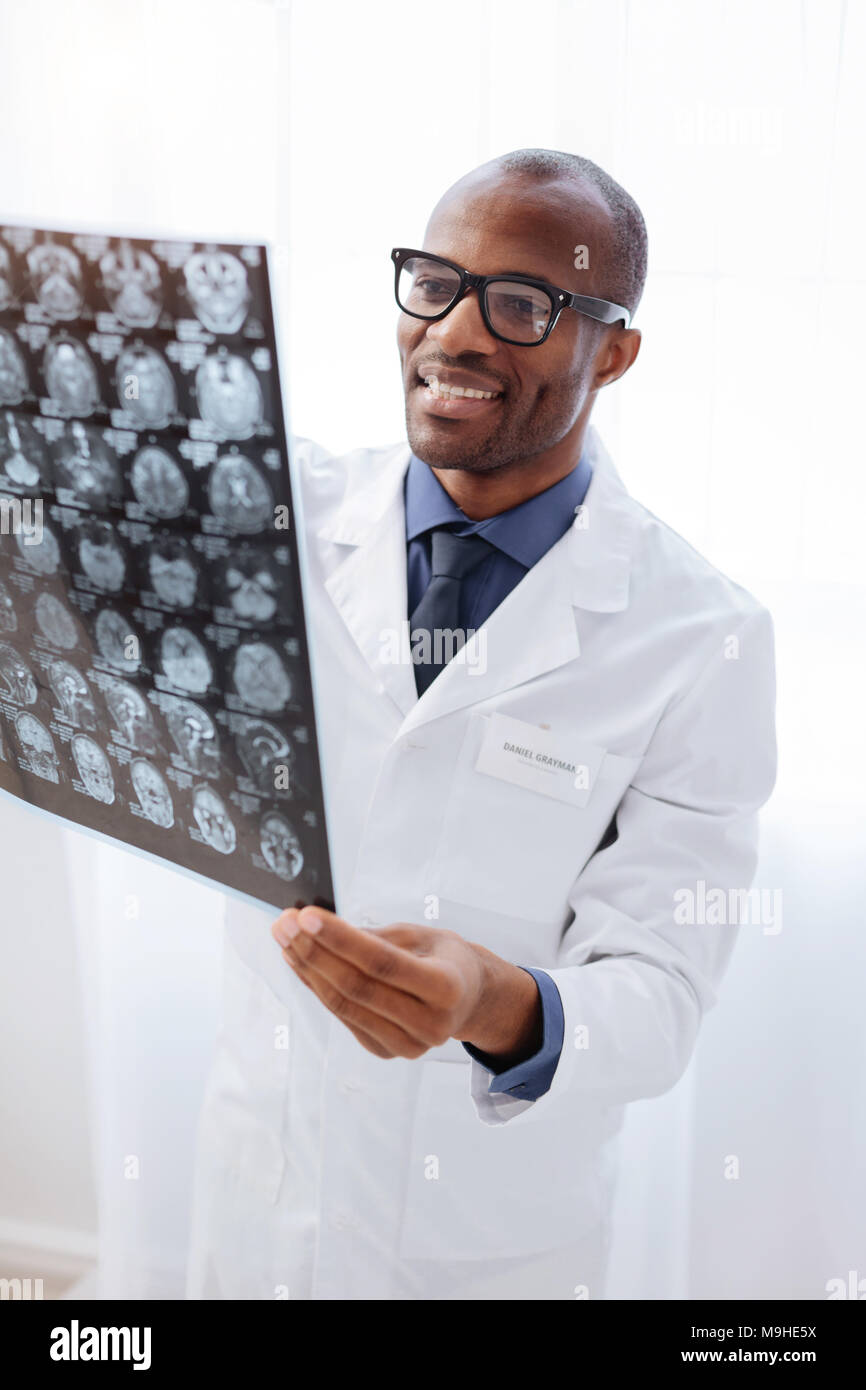 Happy male doctor scrutinizing brain imaging - Stock Image