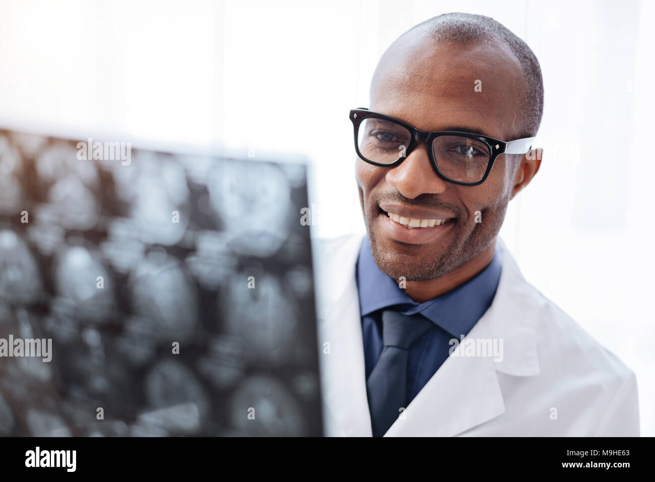 Satisfied male doctor reviewing brain imaging - Stock Image