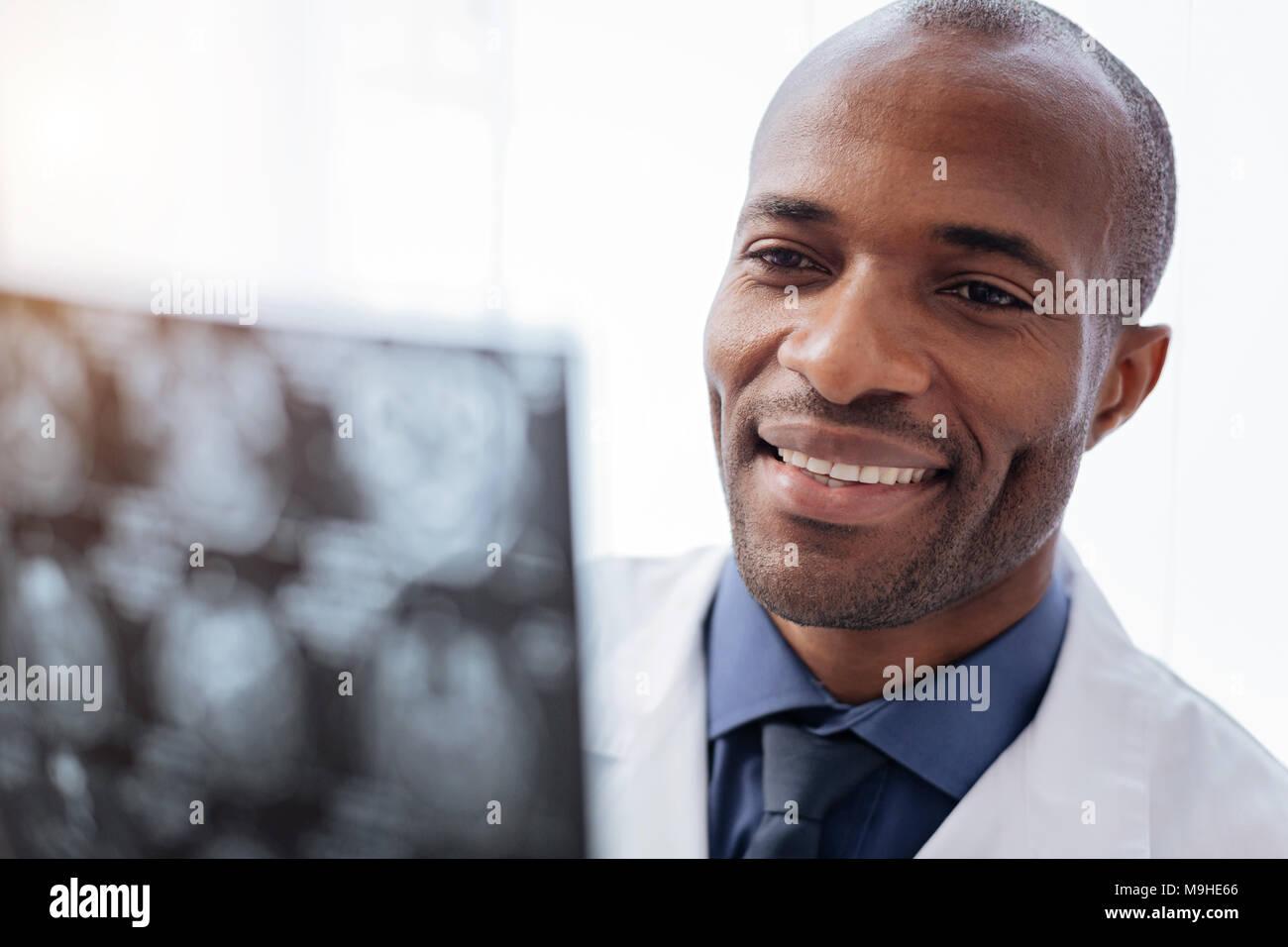 Positive male doctor regarding brain imaging - Stock Image
