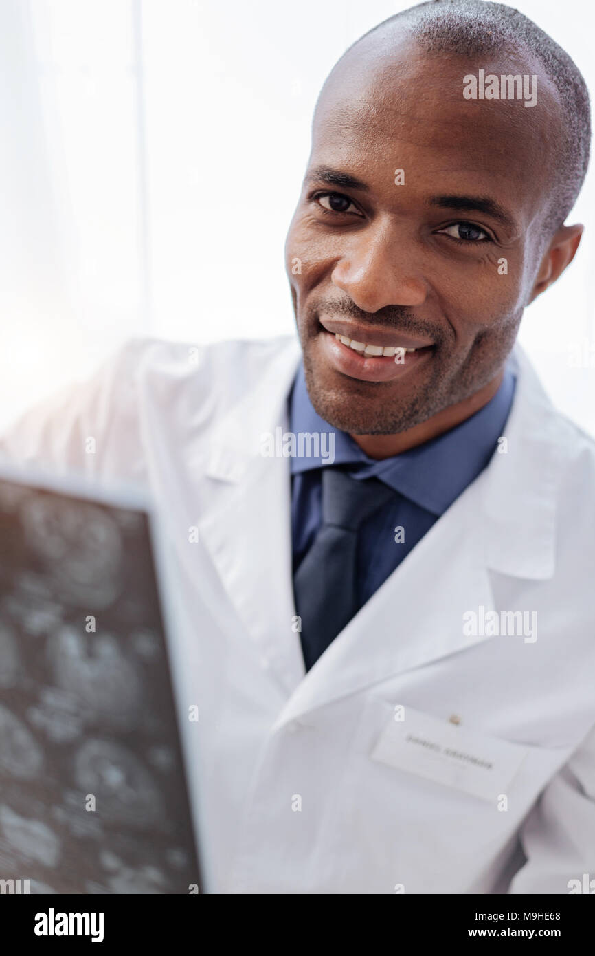 Optimistic male doctor perusing brain imaging - Stock Image