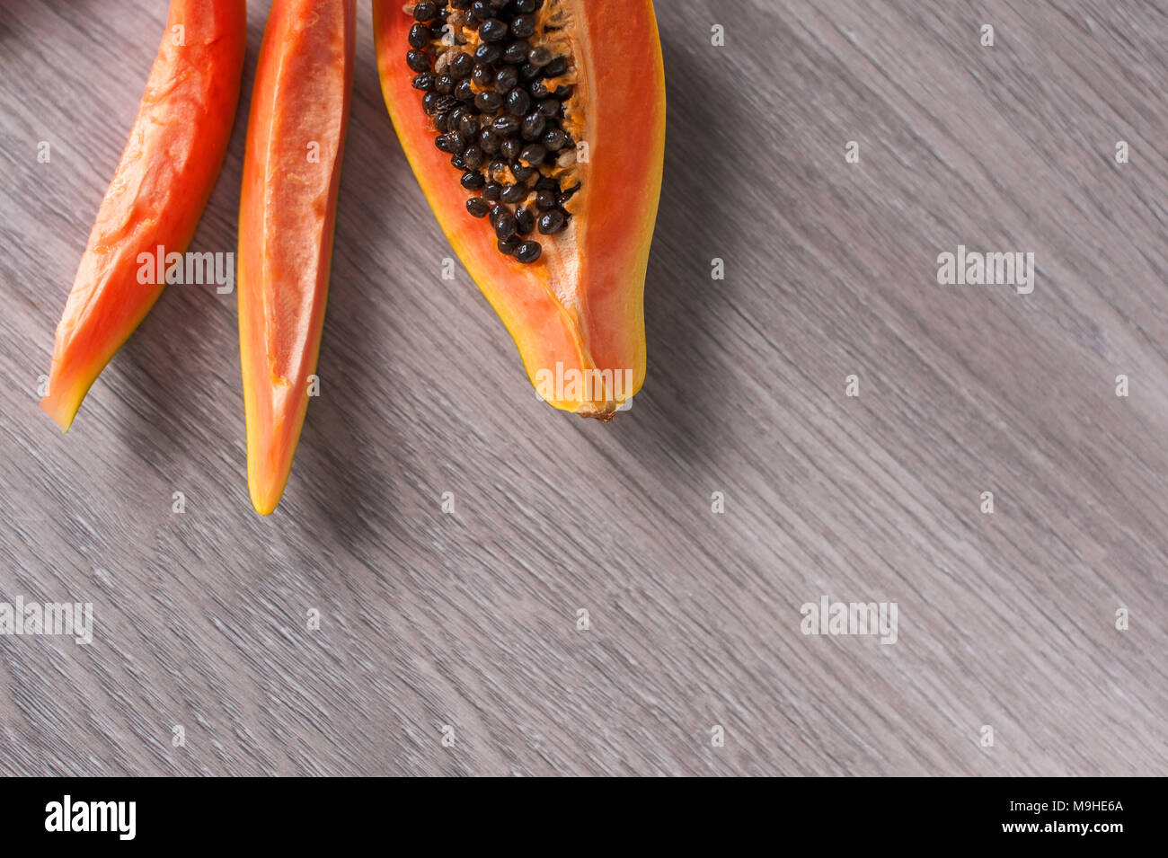 Papaya fruit cut in slices on wooden background Stock Photo