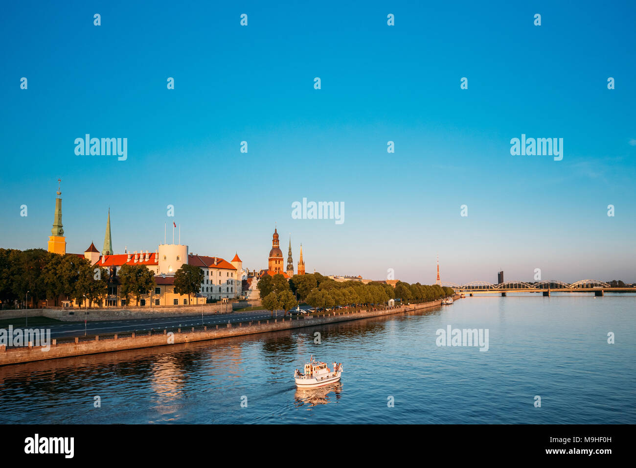 Scenic View To Promenad Of Daugava, In Riga, Latvia. Old Church Towers And Medieval Castle On Background. Seafront Named Ab Dambis. Evening  View With - Stock Image