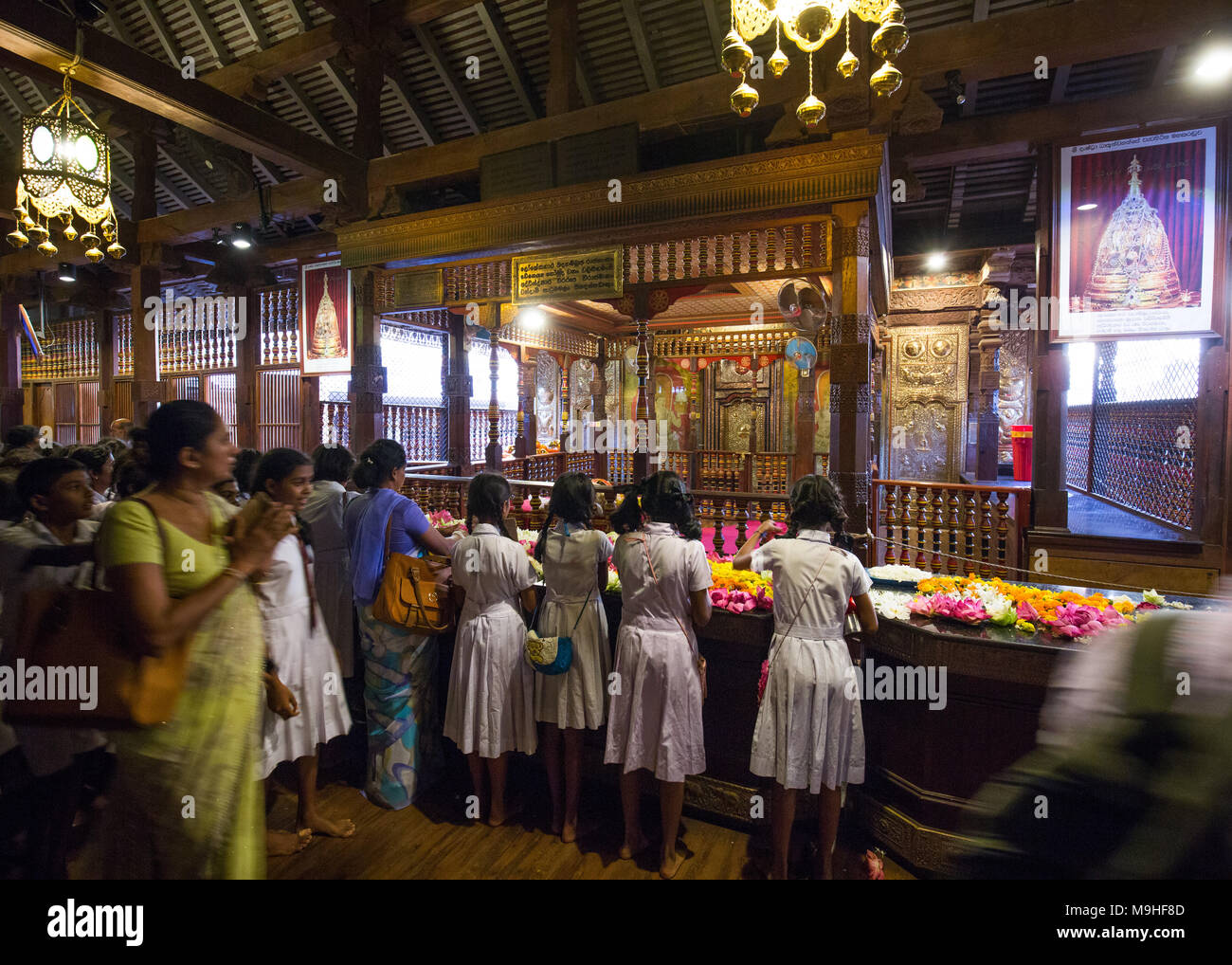 School students and teachers praying inside Temple of the Tooth, Kandy, Sri Lanka, Asia. - Stock Image