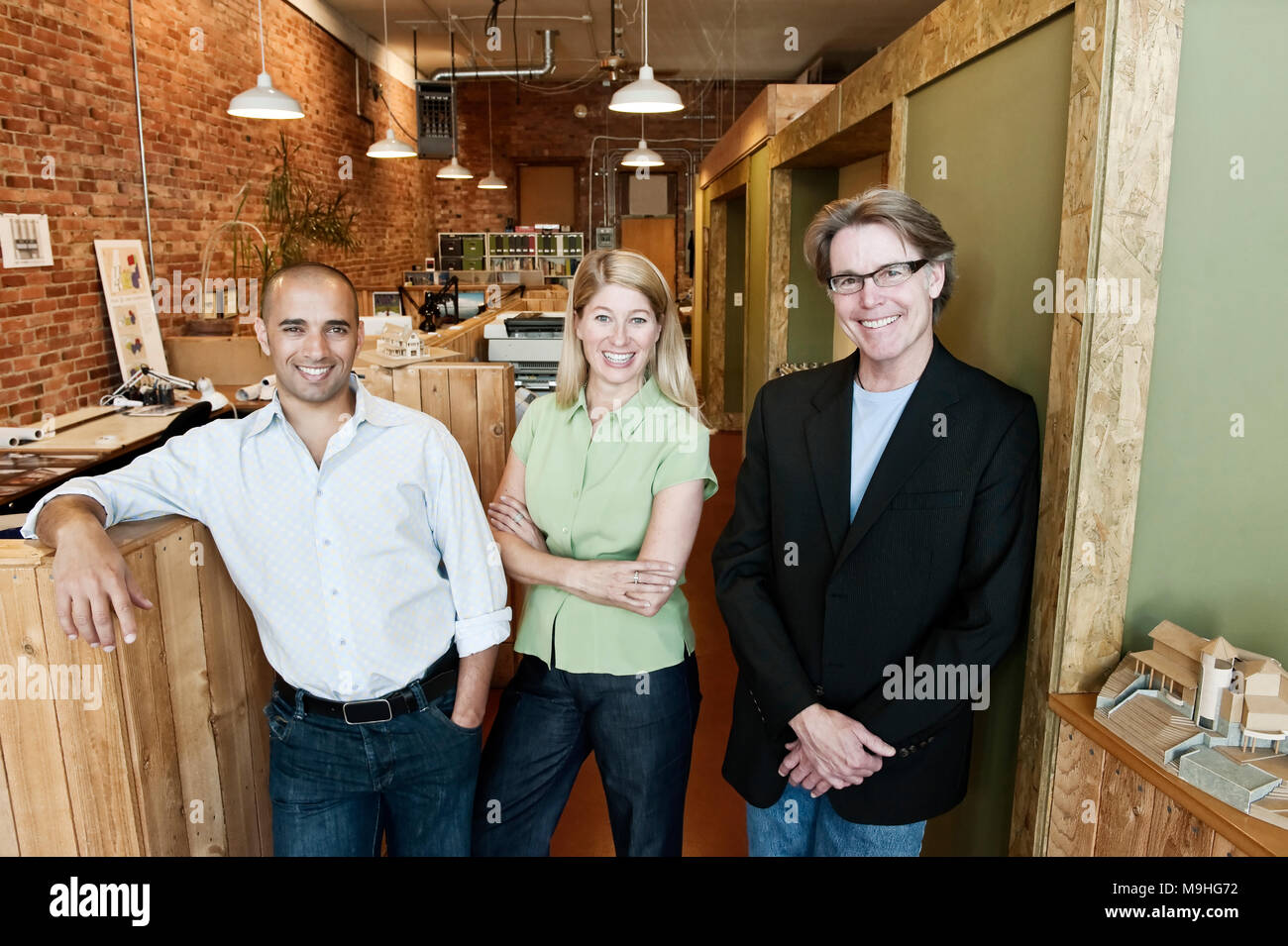 Portrait of a multi-ethnic team of three architects in a small office. - Stock Image