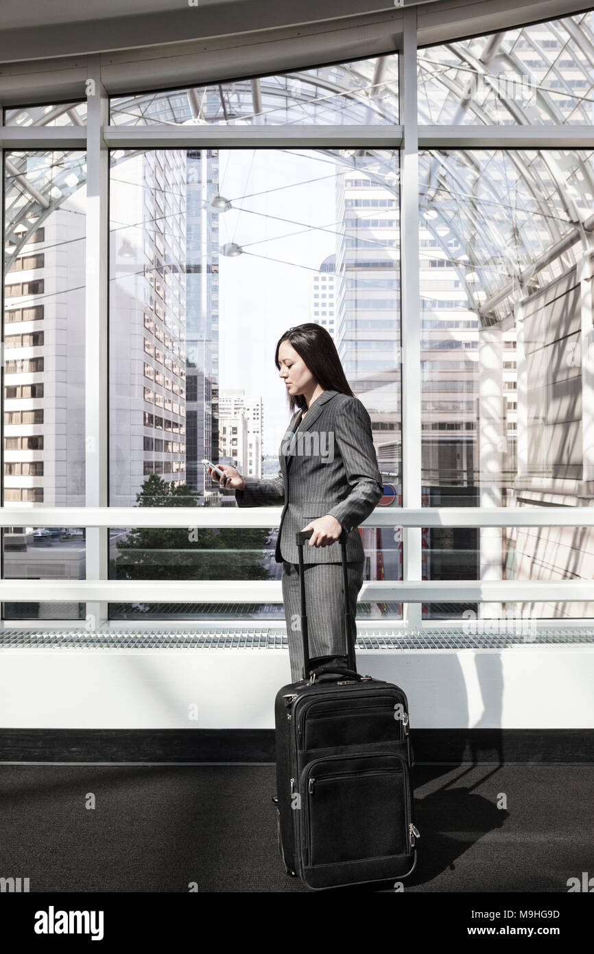 Woman in a business suit standing with her pull along suitcase, using a smart phone, under a glass atrium roof. Business travel. - Stock Image