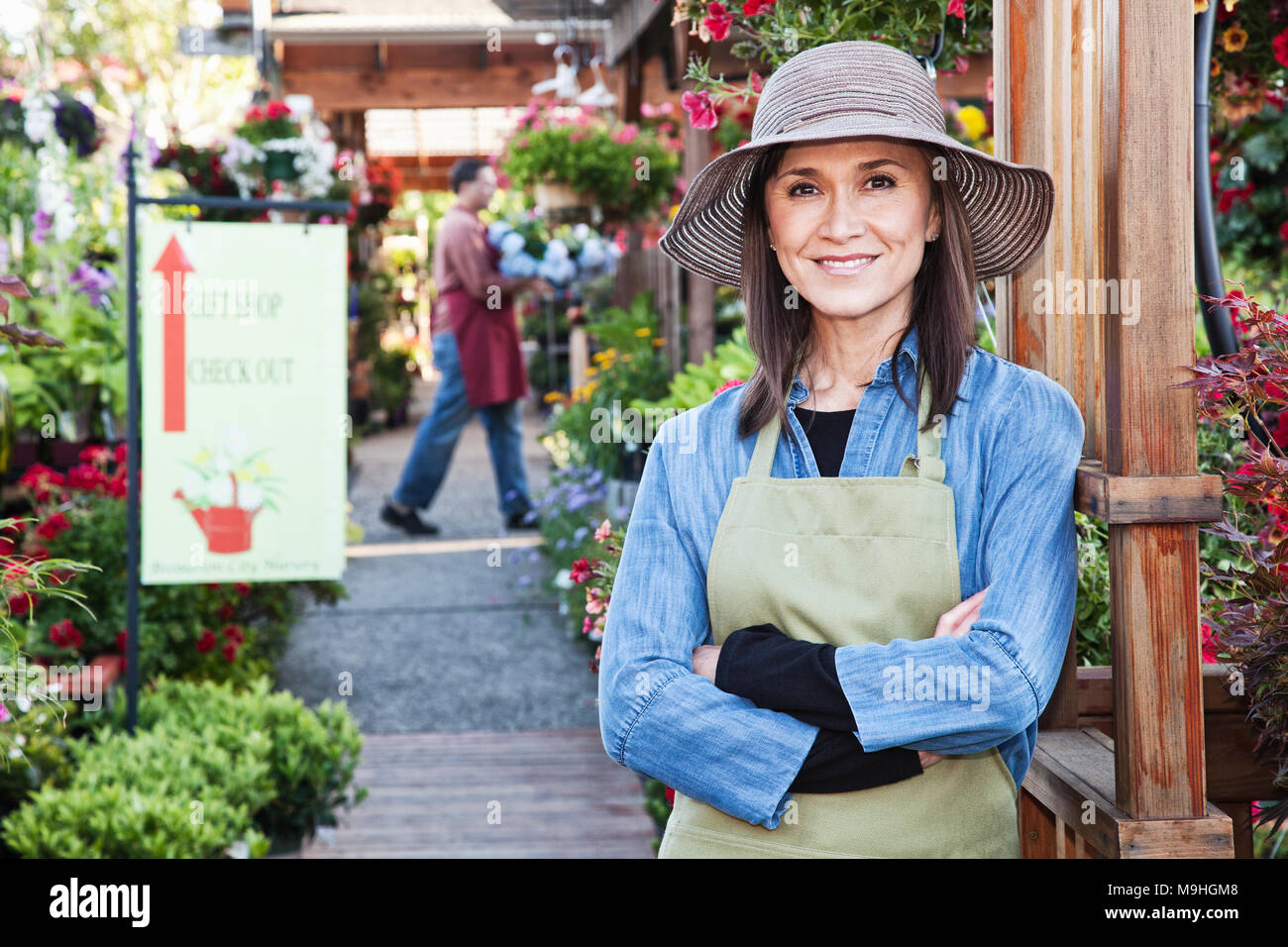 Caucasian woman owner of garden center nursery with a younger employee. - Stock Image