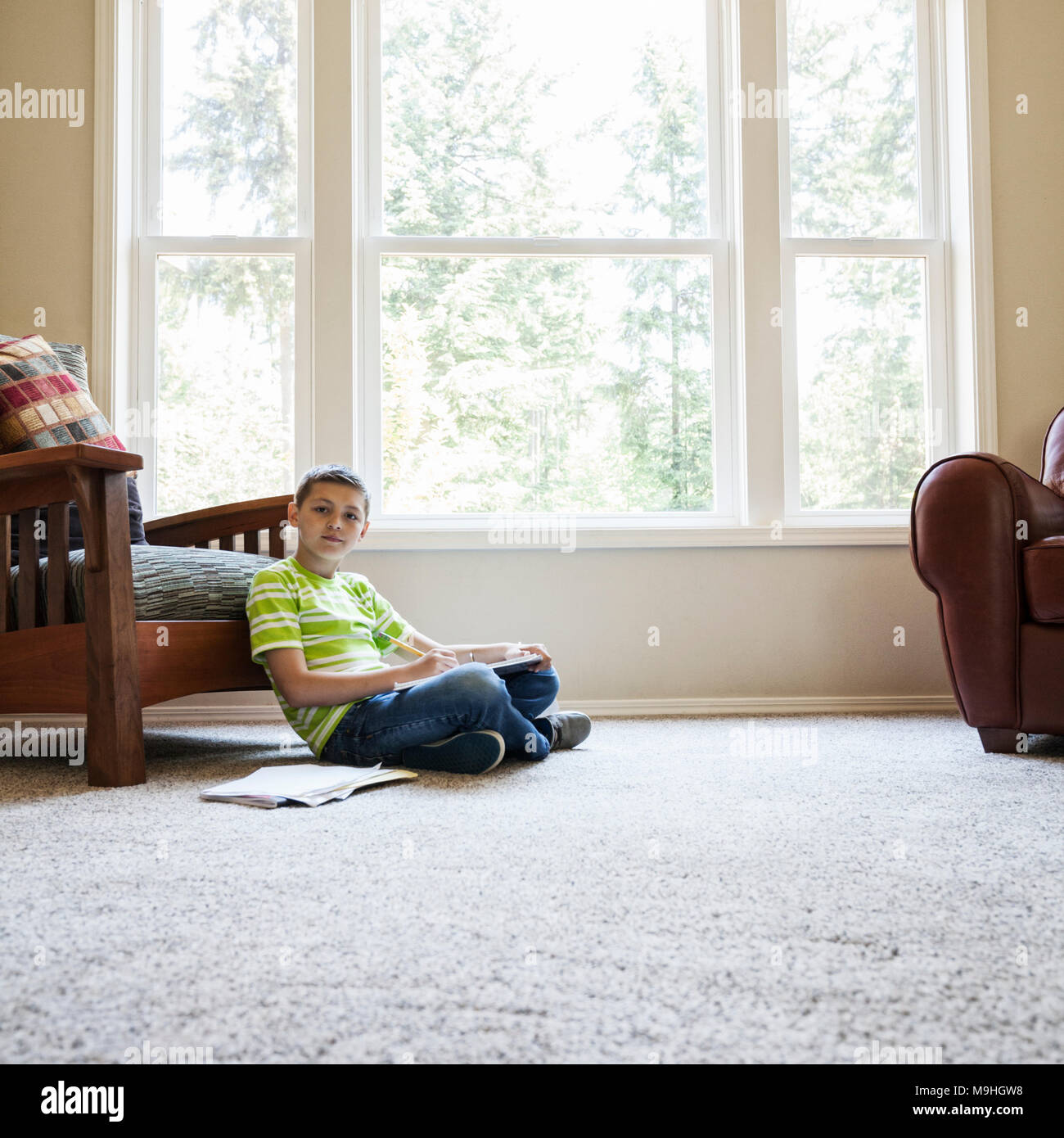 Young boy at home doing homework. - Stock Image