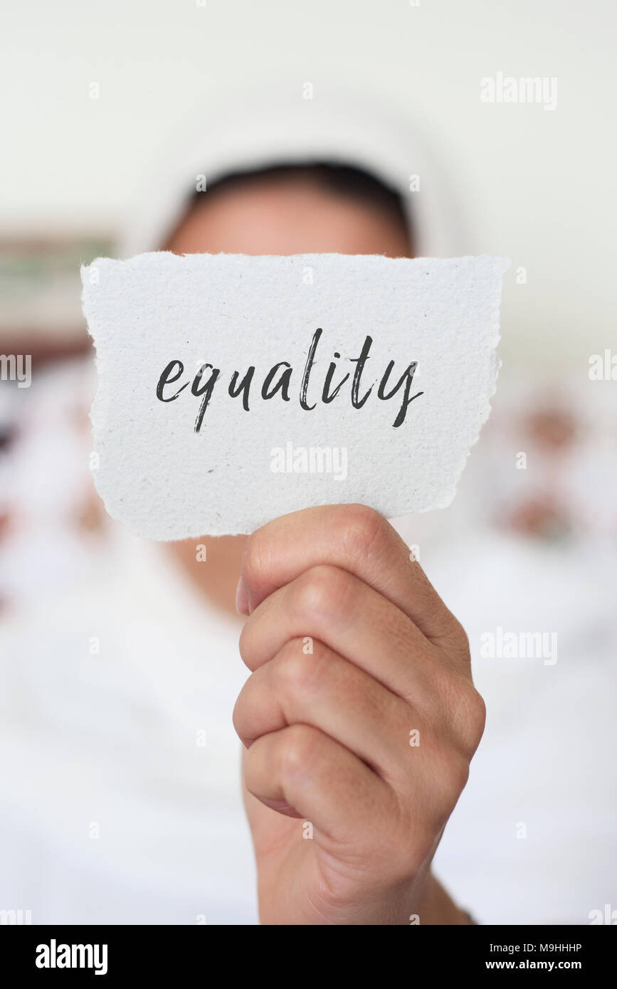 closeup of a young woman indoors wearing a white hijab showing a piece of paper in front of her face with the text equality written in it - Stock Image