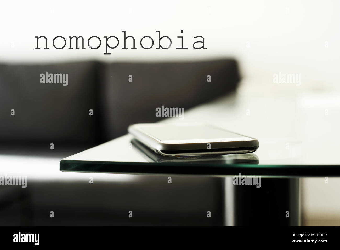 closeup of a smpartphone on a glass table in a modern living room or a lobby, and the text nomophobia, for the phobia of leaving home without the mobi - Stock Image