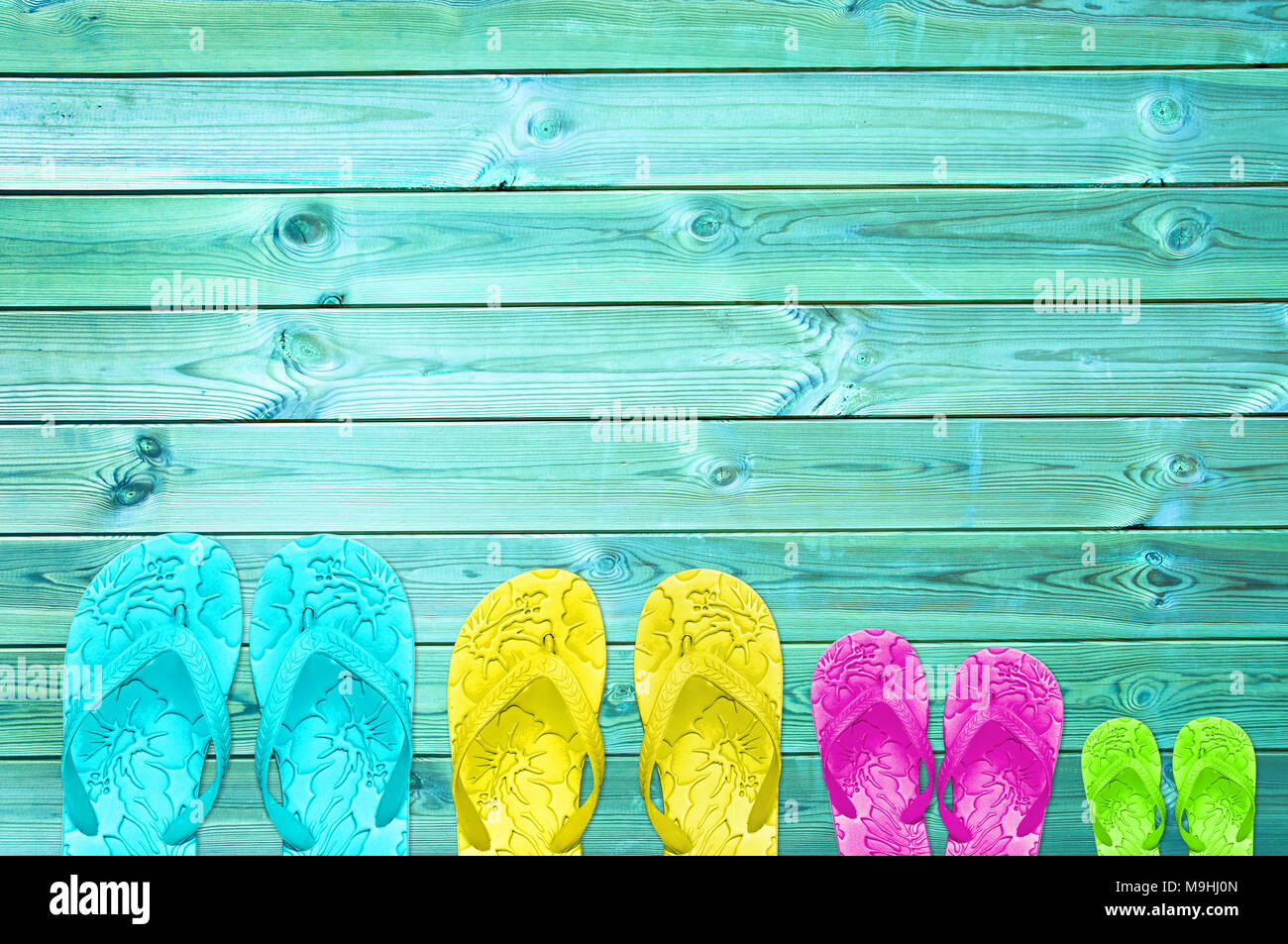 Colorful flip flops of a family of four on a turquoise wood planks background with copy space, family summer beach concept - Stock Image