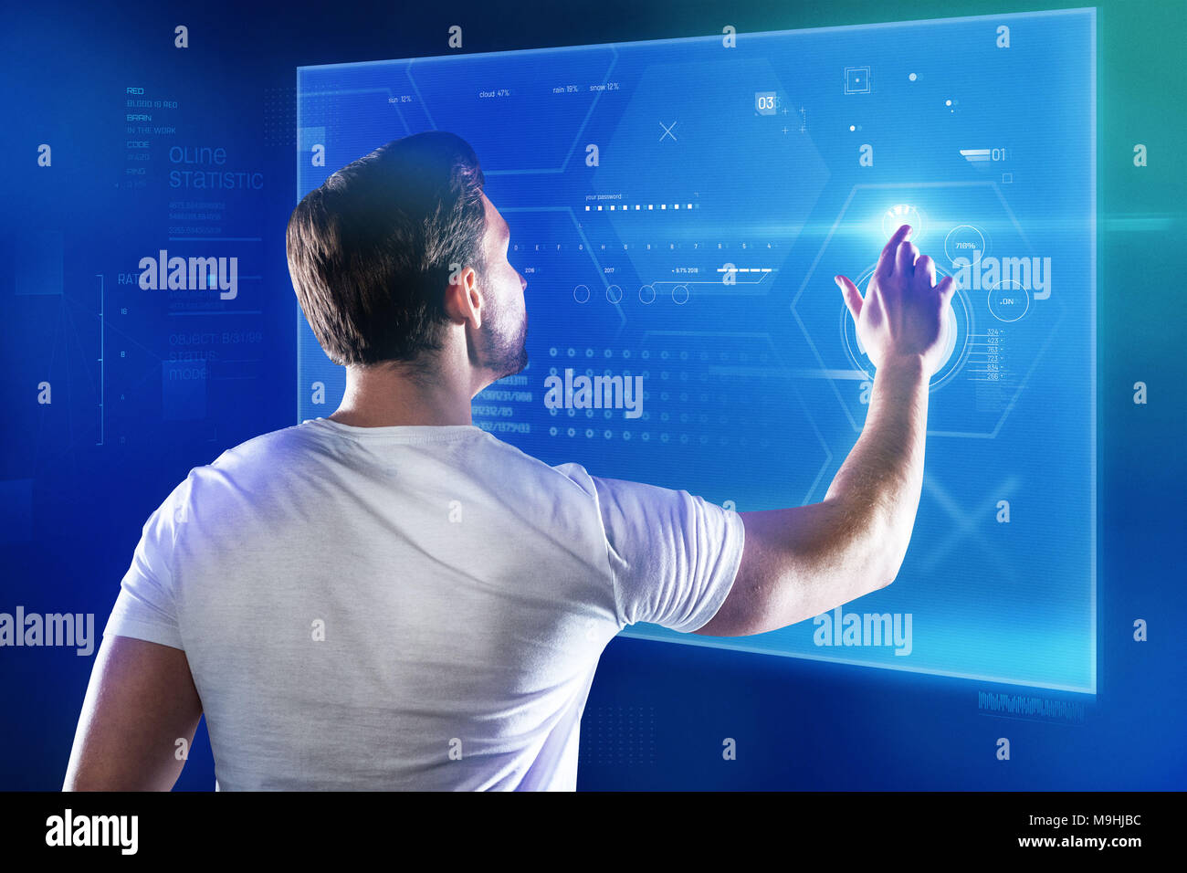 Skilled programmer working with a new device and touching a transparent screen - Stock Image
