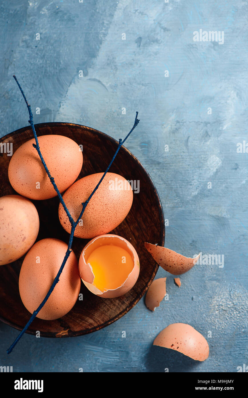 Yolk in an eggshell close-up. Raw cooking ingredients background with copy space. Modern Easter concept with brown hen eggs Stock Photo