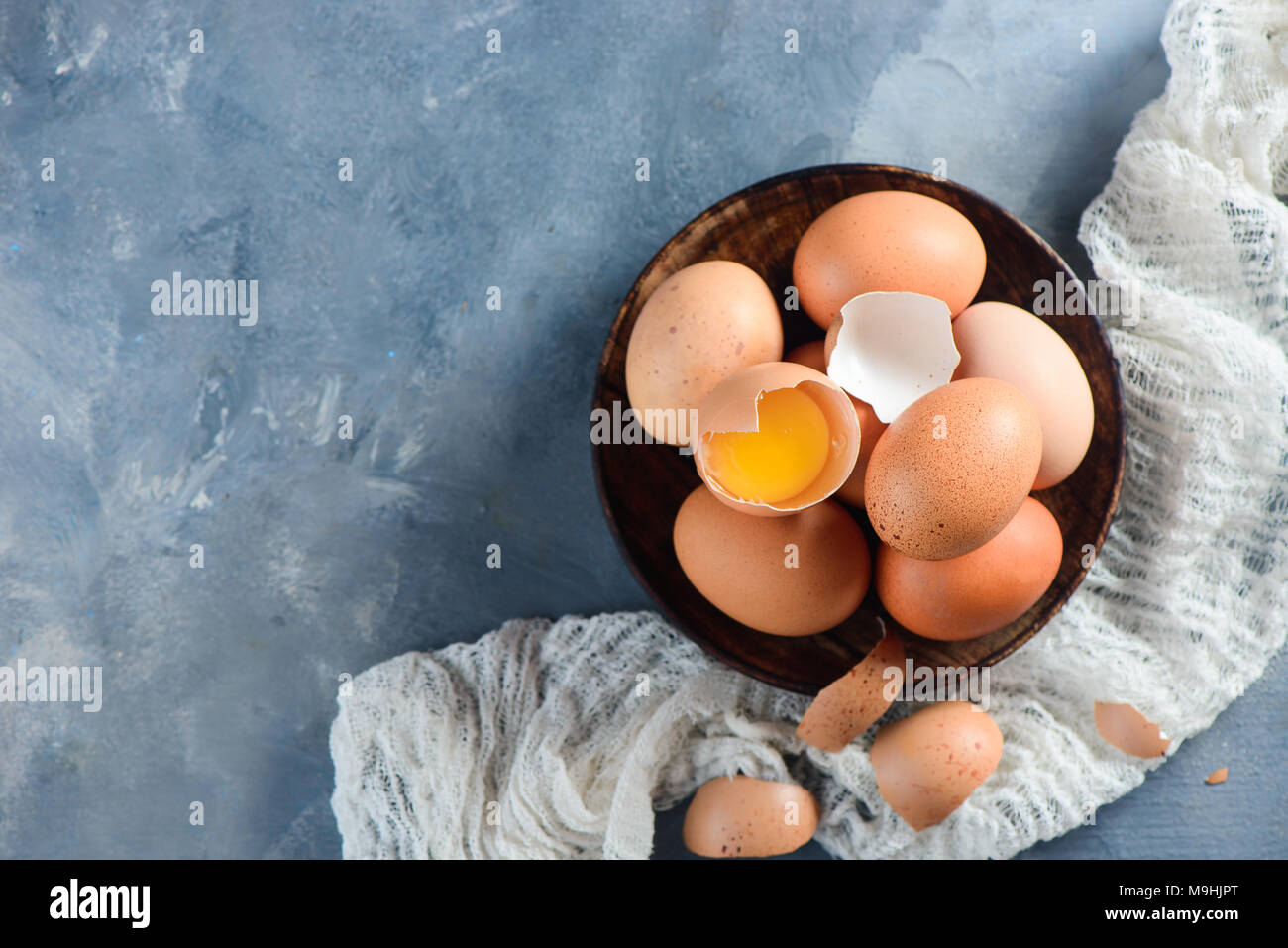 Fresh chicken eggs in a wooden bowl on a concrete background with white cloth. Organic ingredients concept with copy space. - Stock Image