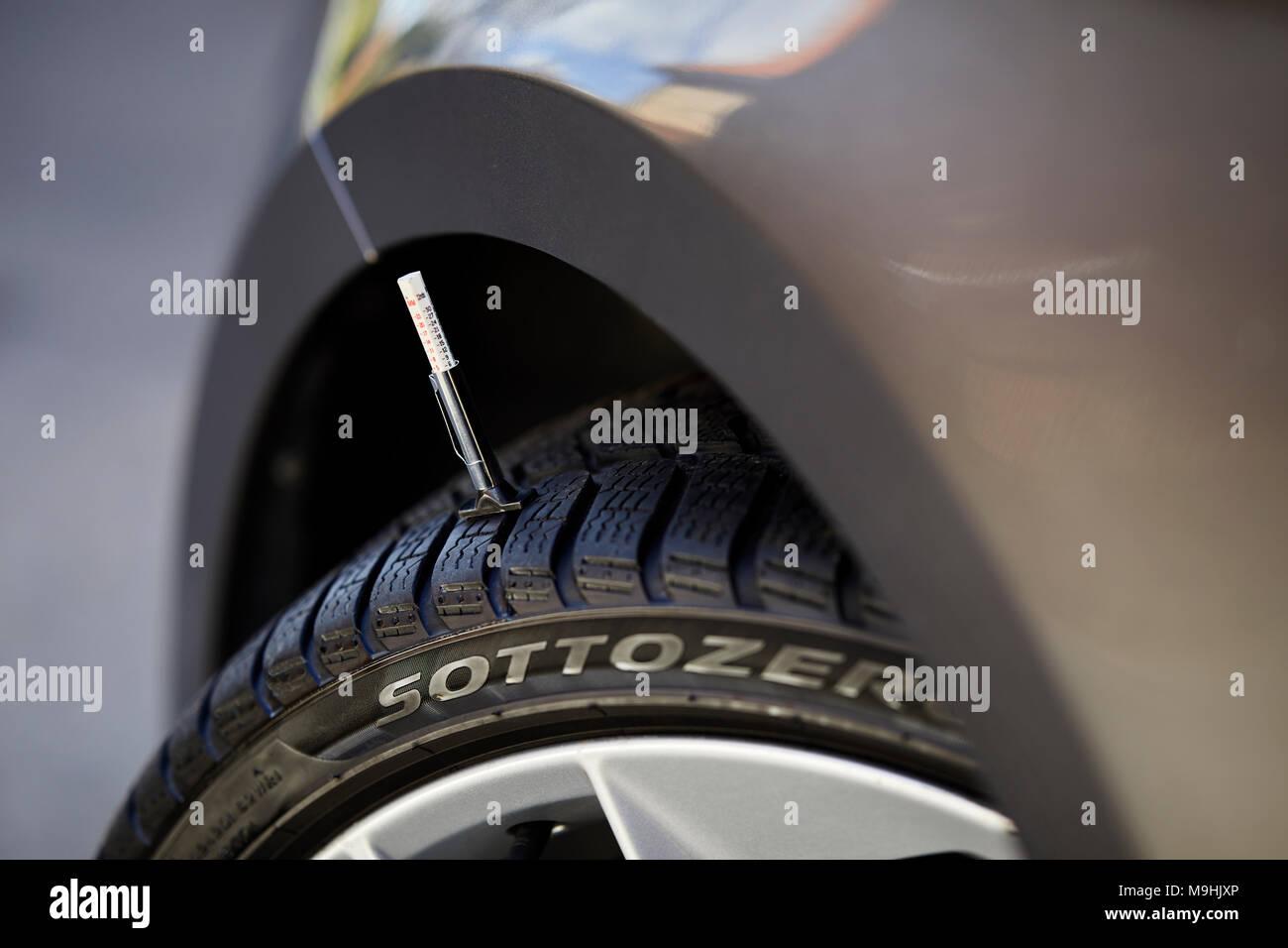 Taking tyre tread depth gauge readings - Stock Image