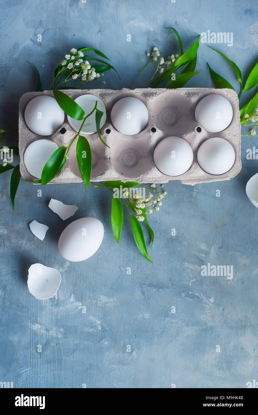 Chicken eggs, whole and broken, in a paper packaging on a concrete background with green leaves and spring flowers. Eco cooking concept with copy space. - Stock Image