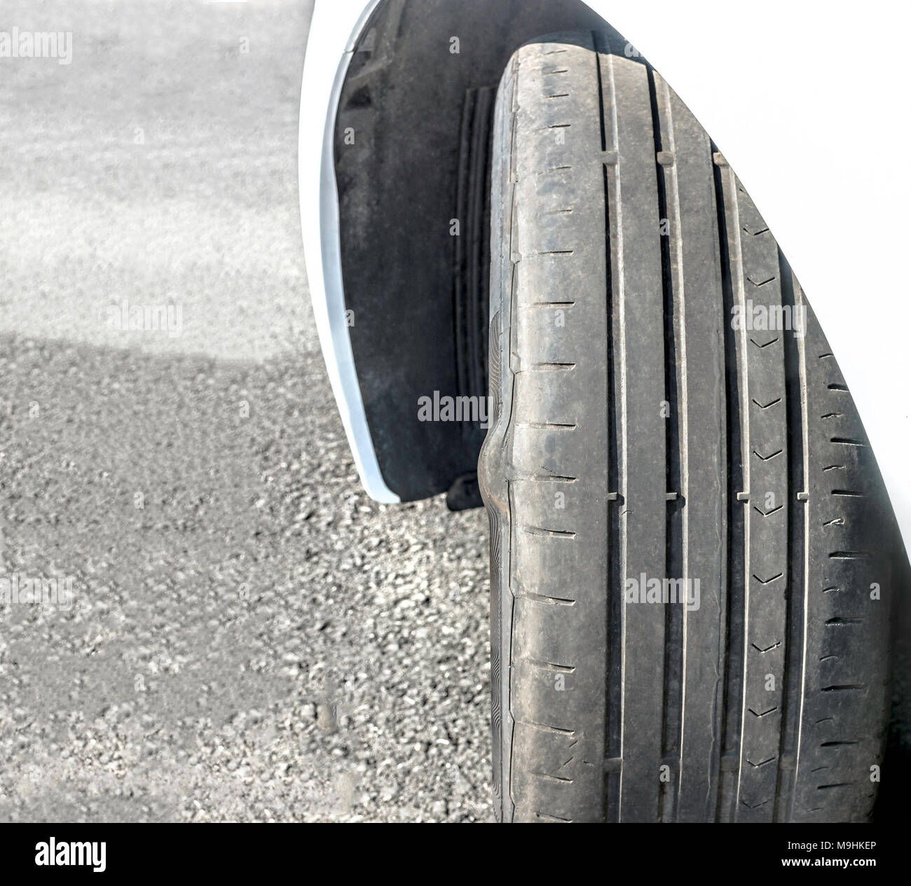 Badly worn out car tire tread and damaged bulb like side due to wear and tear or because of poor tracking or alignment of the wheels, dangerous. - Stock Image