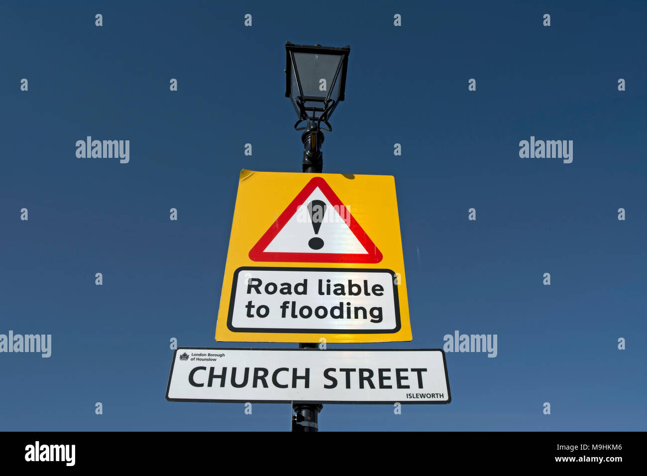 street name sign for church street, isleworth, middlesex, england, below a road liable to flooding warning sign Stock Photo