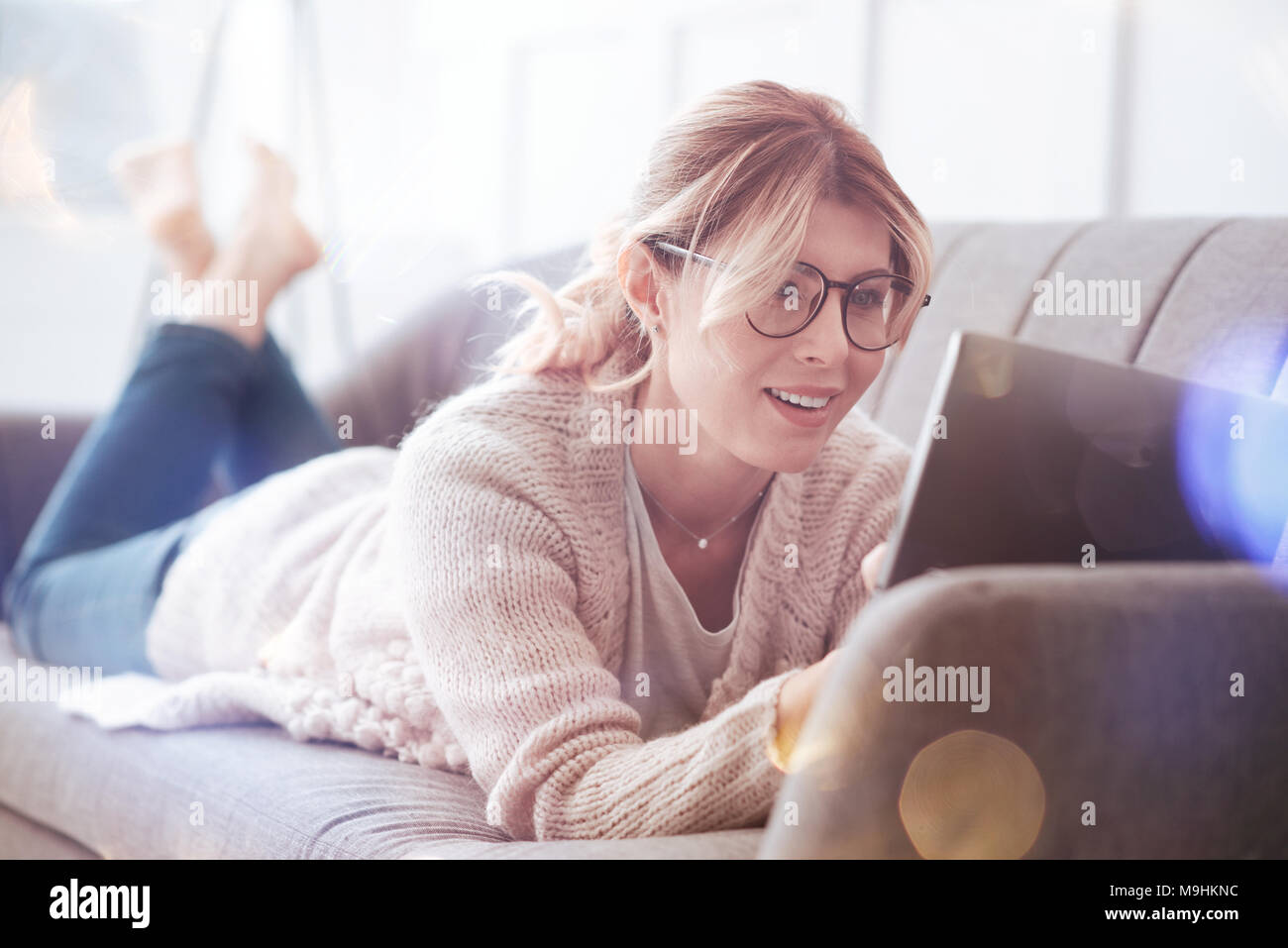 Cheerful pretty woman surfing on the Internet - Stock Image
