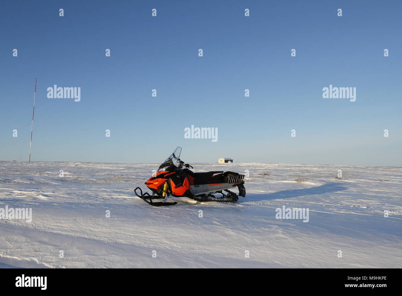 A red snow machine on a white winter arctic landscape with snow on the ground a blue endless sky, near Arviat Nunavut Canada - Stock Image
