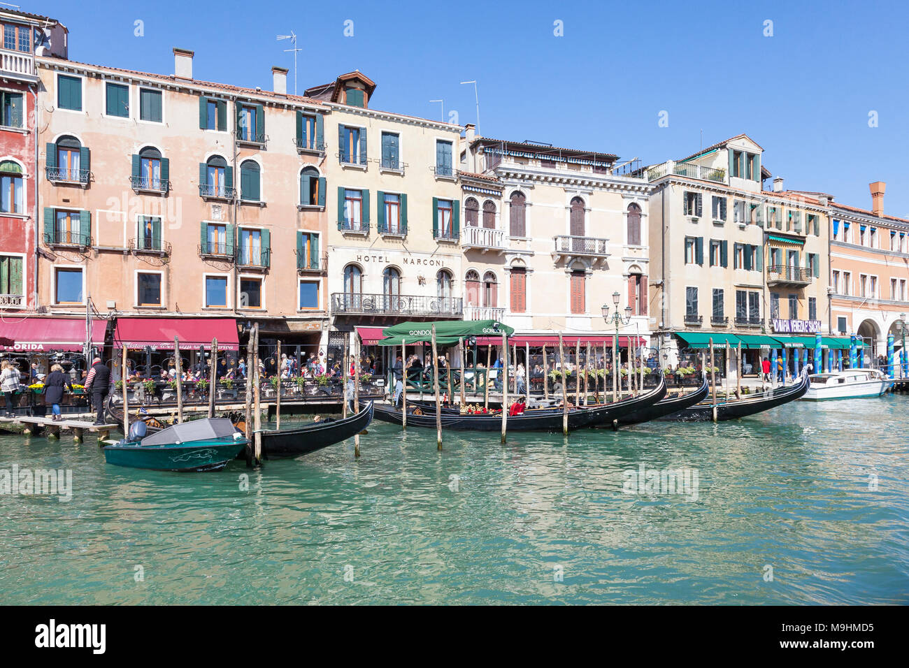 Tourists eating at restaurants (tavern, trattoria) along Riva del Vin, San Polo, Grand Canal, (Canal Grande) Venice, Veneto, Italy with historic palaz - Stock Image