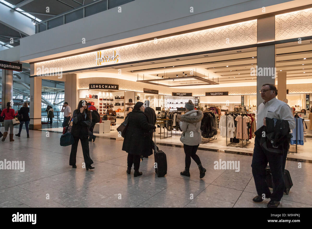 Departing air travel passengers outside Harrods retail outlet in Heathrow Airport, Terminal Five, London, England, UK. - Stock Image