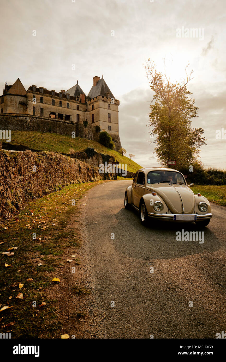 A classic VW Beetle drives past the Château de Biron a castle in the valley of the Lède in the commune of Biron in the Dordogne France. - Stock Image