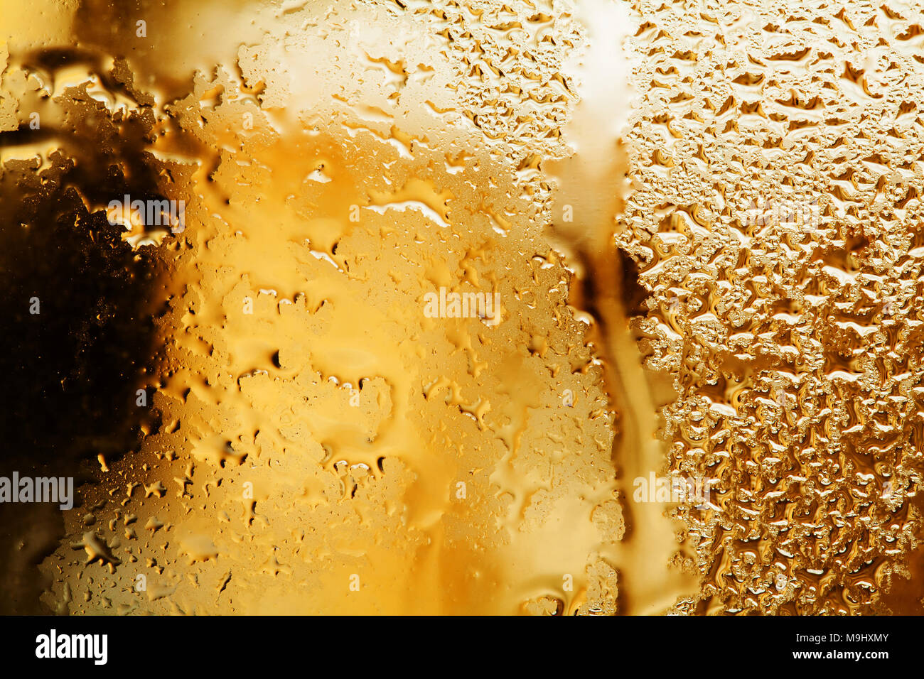 Rainy weather concept. Abstract golden color frame and water droplet pattern on glass window. Liquid textured bubbles macro view. Shallow depth of field. Stock Photo
