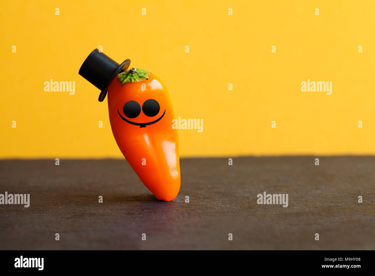 Funny senor pepper, decorated sunglasses mustache, black hats. Funny old fashioned orange vegetable character, black stone yellow background. Creative food design poster. - Stock Image