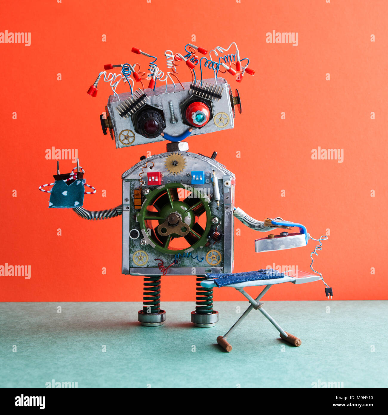 Robotic ironing service concept. Big robot housework assistant ironing blue jeans with iron on the board. Orange wall, green floor - Stock Image