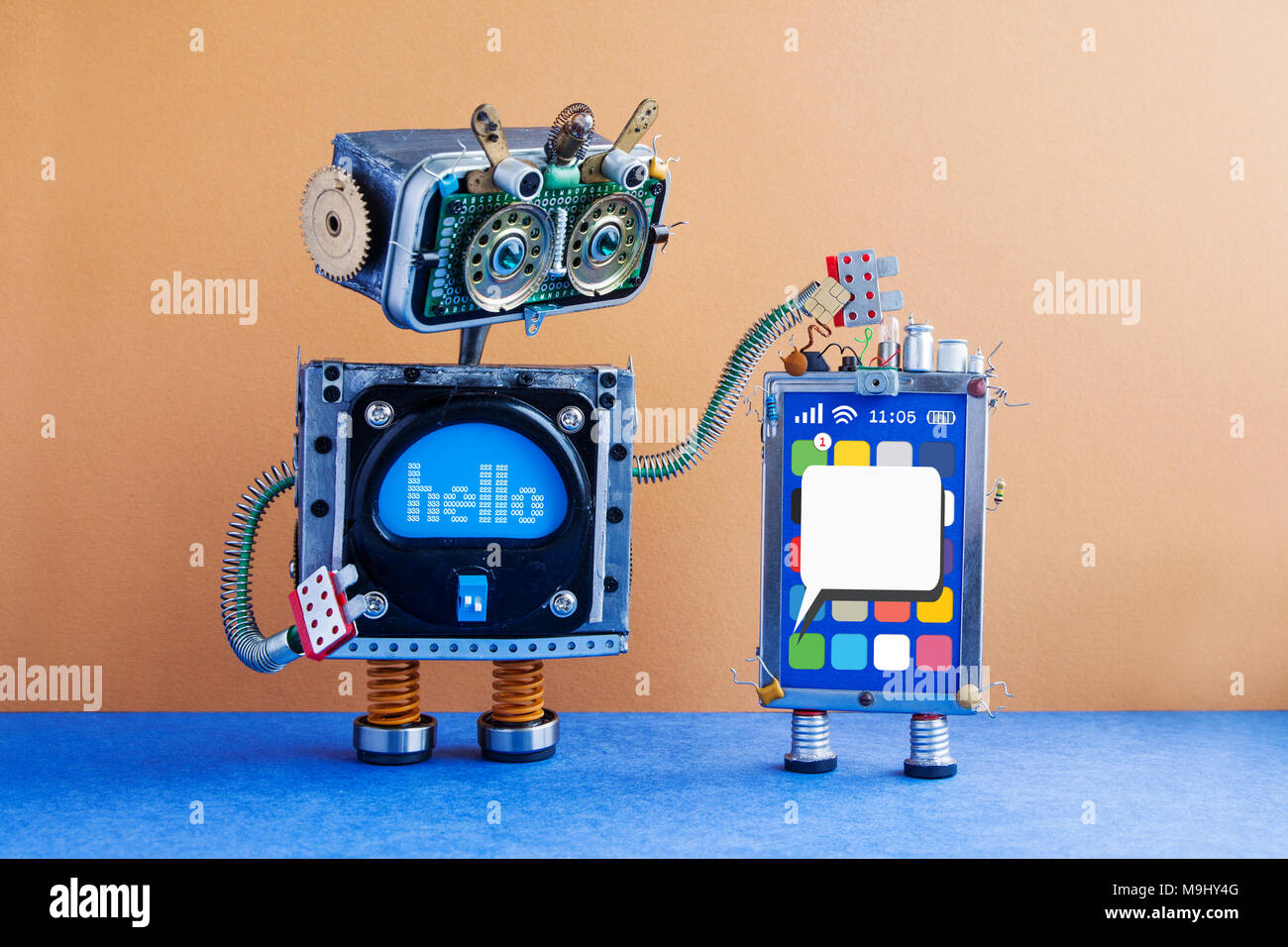 Big robot and mobile smartphone gadget. Funny robotic toy characters, creative design touch screen phone device, light bulb capacitors sim card. Blank sms message on display. Brown wall, blue floor background. - Stock Image