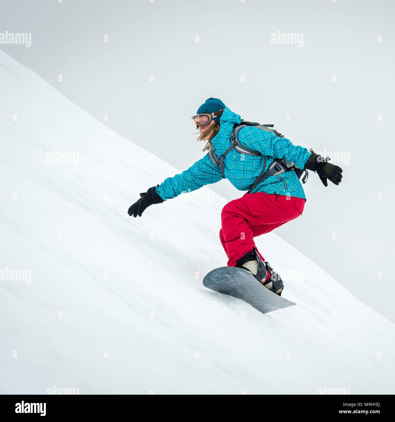 pretty young woman on the snowboard riding in the mountains Stock Photo